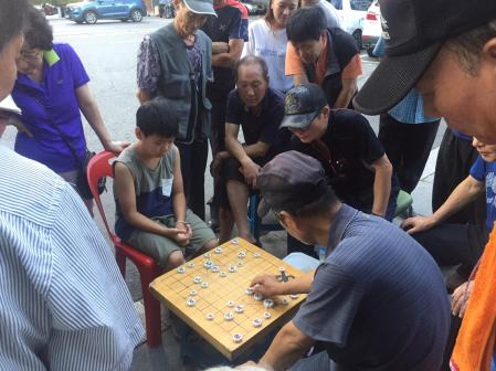 An old man and a child go head to head in a game of Go